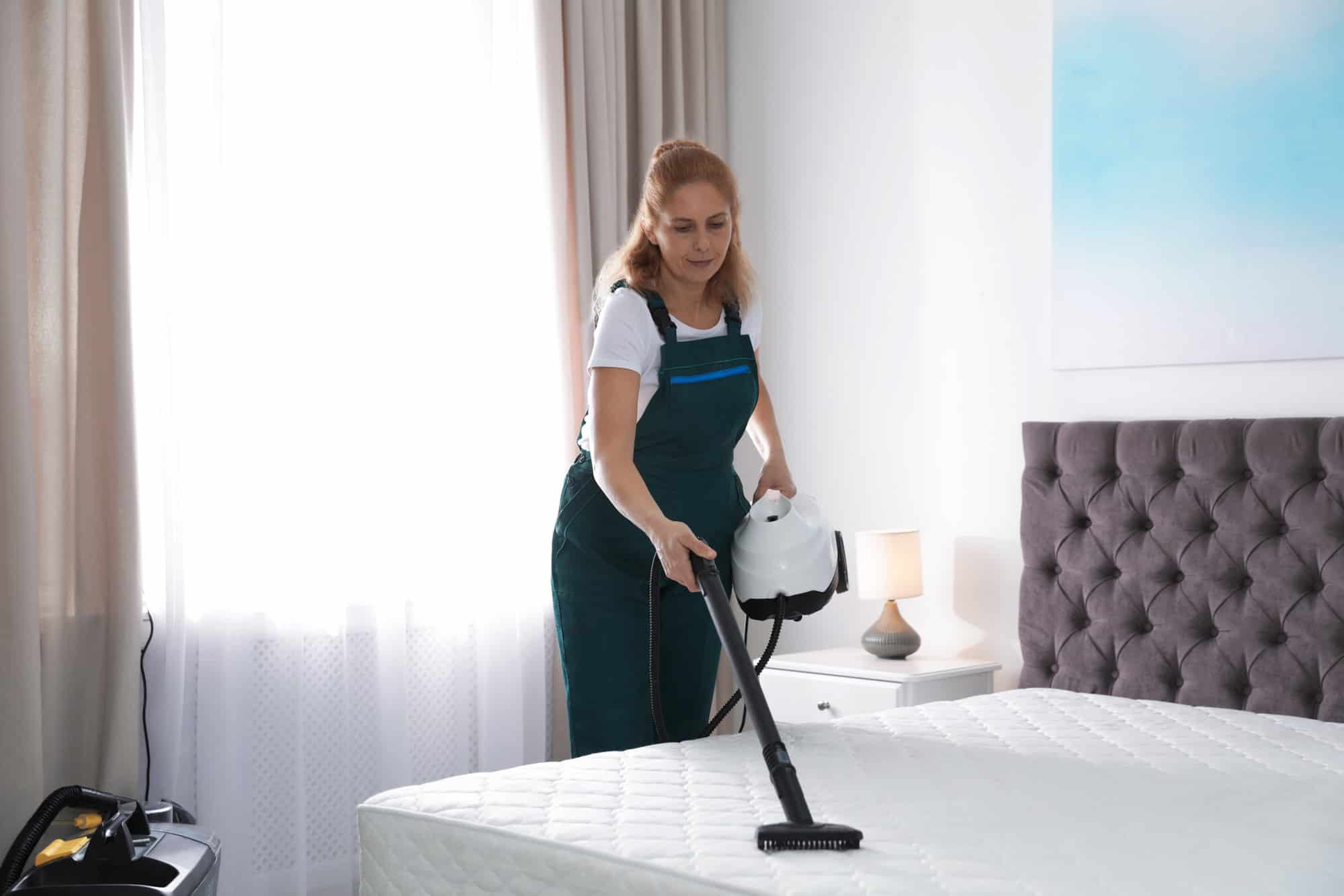 janitor professionally steam cleaning mattress