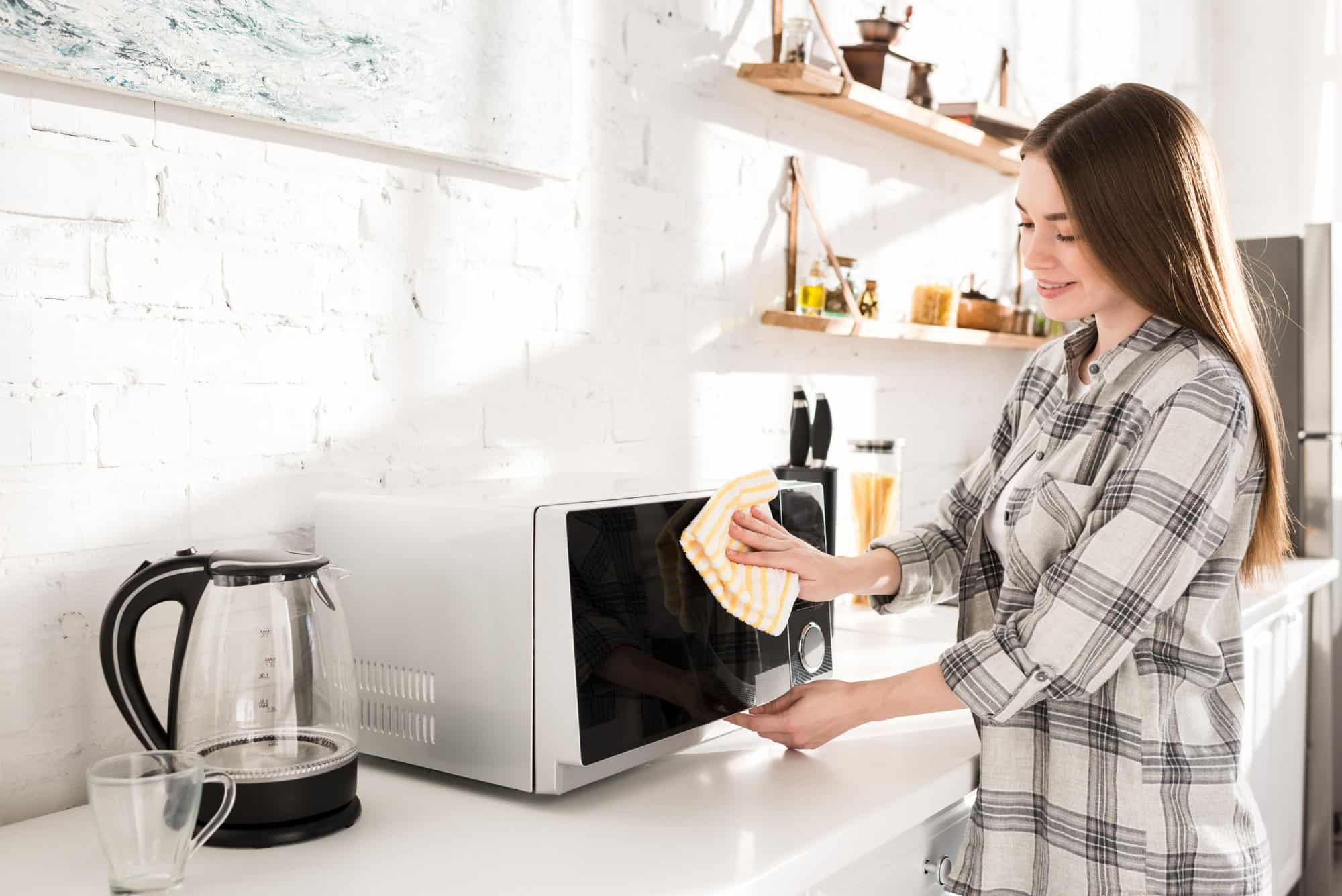 girl finished cleaning a microwave looking happy