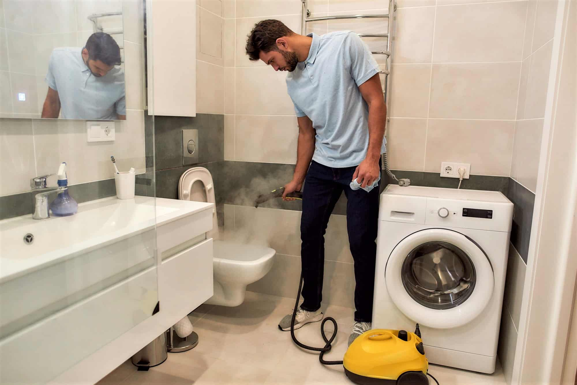 Young man steam cleaning a toilet and bathroom
